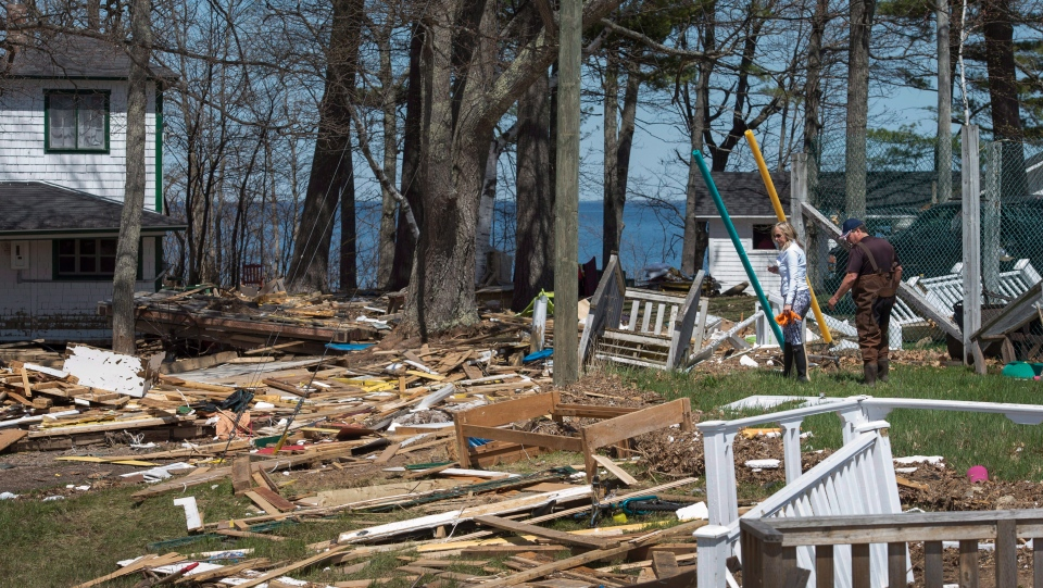 Michelle and Leo Cain look for belongings in debris from homes and cottages destroyed by the floodwater from the Saint John River in Robertson's Point, N.B., on Sunday, May 13, 2018. (THE CANADIAN PRESS/Darren Calabrese)