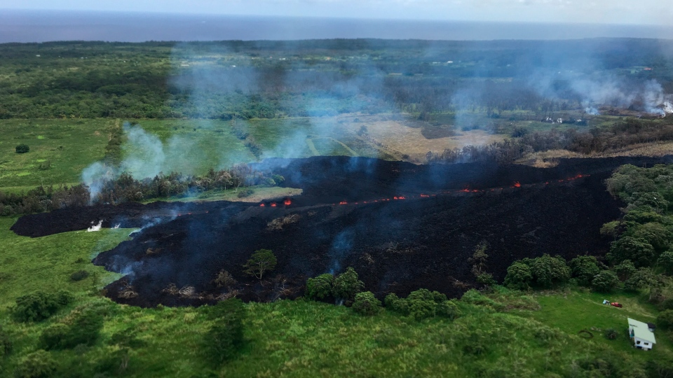 In this May 13, 2018 photo released by the U.S. Geological Survey, gases rise from a fissure near Pahoa, Hawaii. (U.S. Geological Survey via AP)