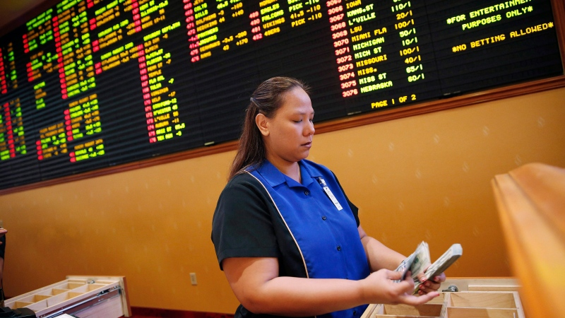 In this Aug. 20, 2015, file photo, Therese Duenas counts money as she takes bets in the sports book at the South Point hotel and casino in Las Vegas.  (AP Photo/John Locher, File)