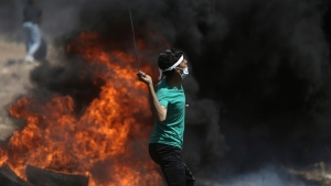 A Palestinian protester hurls stones at Israeli troops during a protest at the Gaza Strip's border with Israel, Monday, May 14, 2018. (AP / Khalil Hamra)