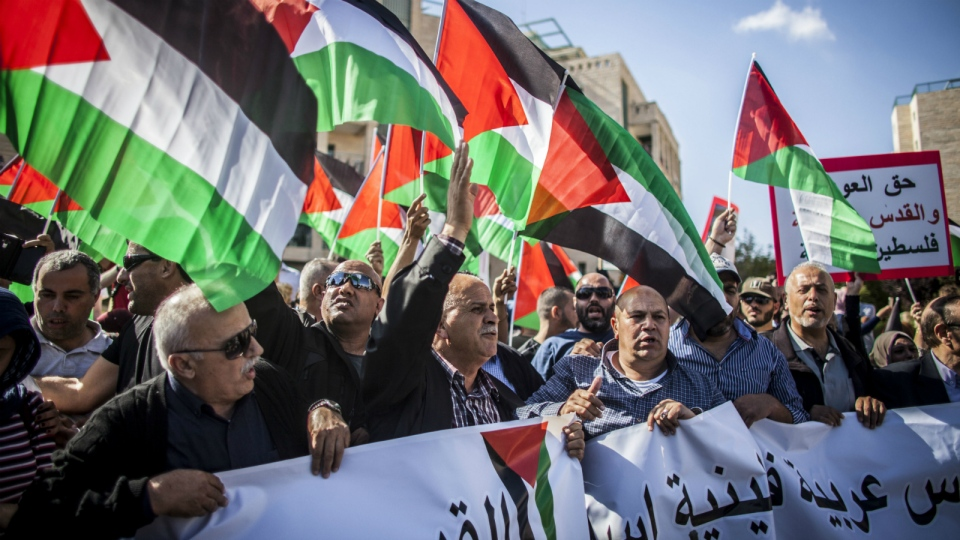 Israeli and Palestinian protesters wave signs and chant outside the new U.S. Embassy in Jerusalem Monday May 14, 2018. (AP Photo/Eyal Warshavsky)