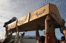 Iraqis lift up a casket of a victim of a bombing in Baghdad for the funeral in the holy Shiite city of Najaf, 160 kilometres south of Baghdad, Iraq on Nov. 9, 2006. (AP / Alaa al-Marjani)