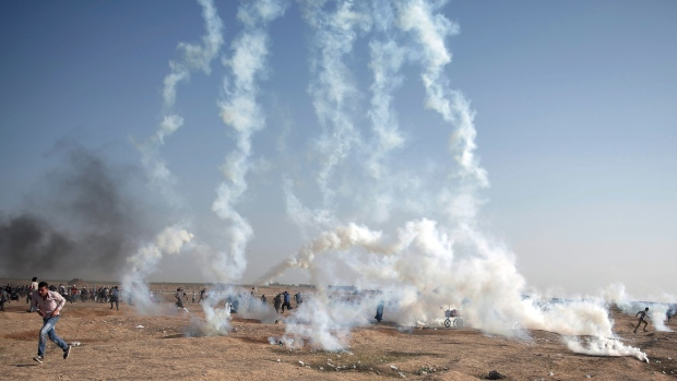 Palestinian protesters run for cover from teargas fired by Israeli troops during a protest at the Gaza Strip's border with Israel, Tuesday, May 15, 2018. (AP Photo/Khalil Hamra)