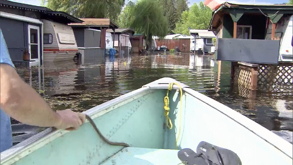 Bubba Brandt walks beside a boat during a tour of a flooded mobile home park in Christina Lake, B.C. on Wednesday, May 16, 2018.