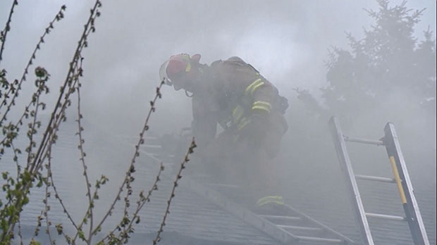 A firefighter checks the roof of a townhouse in the Killarney area.