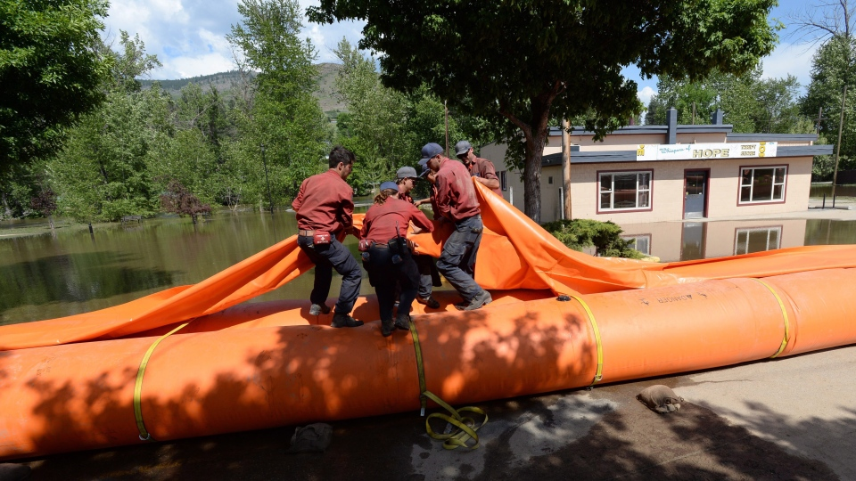 Wildfire service workers install a water dyke near the Kettle River in Grand Forks, B.C., on Wednesday, May 16, 2018. (Jonathan Hayward/THE CANADIAN PRESS)