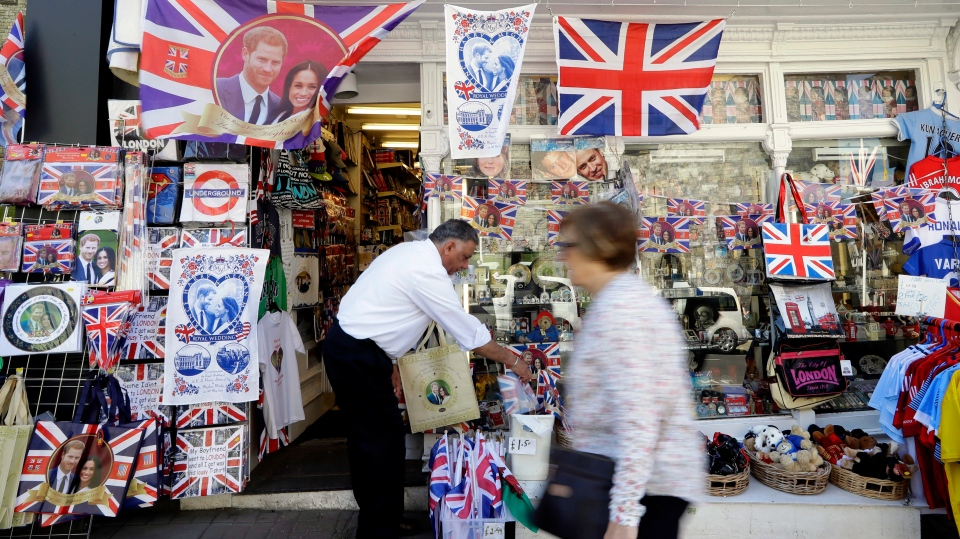 A woman passes a shop window decorated with wedding memorabilia in Windsor, England, Monday, May 14, 2018. (AP Photo/Kirsty Wigglesworth)