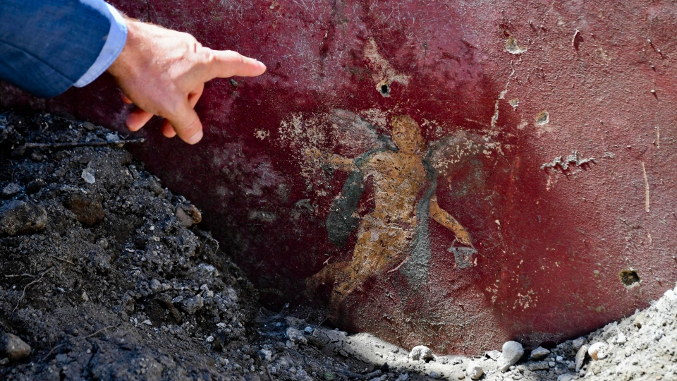 A man points at a detail of a fresco that was found during excavation works in the archaeological site of Pompeii, Thursday, May 17, 2018. (Ciro Fusco /ANSA via AP)