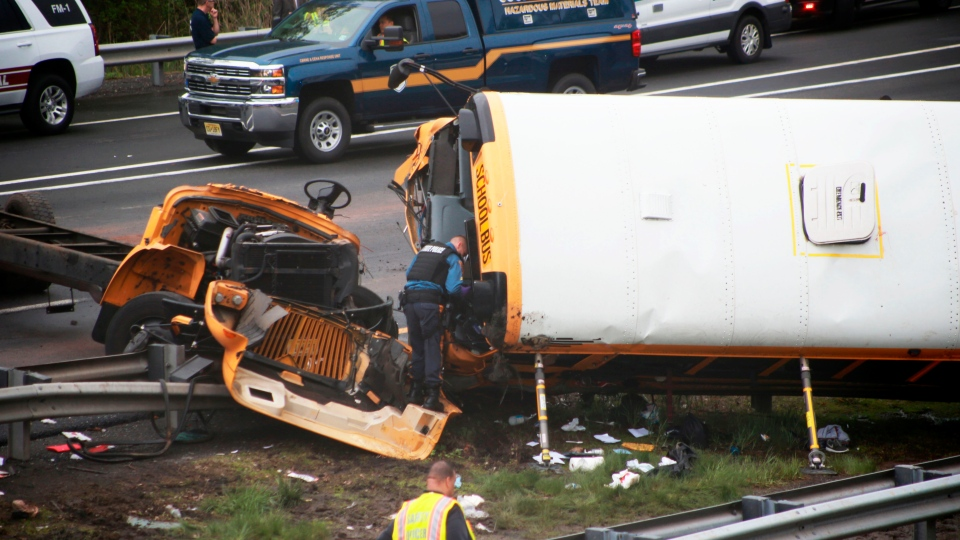 Emergency personnel examine a school bus after it collided with a dump truck collision, injuring multiple people, on Interstate 80 in Mount Olive, N.J., Thursday, May 17, 2018. (Ed Murray/NJ Advance Media via AP)