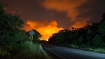 Volcanic activity from the Malama Ki and Leilani Estates neighborhoods glows in the distance from Hwy 137, Thursday, May 17, 2018, near Pahoa, HI. (AP Photo/Marco Garcia)