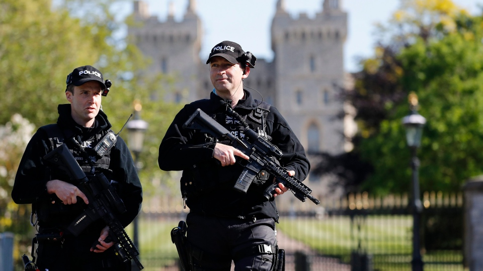 Armed police officers patrol in front of Windsor Castle in Windsor, England, Thursday, May 17, 2018. (AP Photo/Frank Augstein)