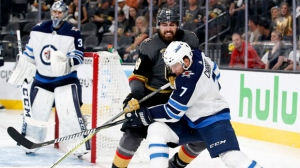 Winnipeg Jets defenseman Ben Chiarot, right, passes the puck around Vegas Golden Knights right wing Alex Tuch during the second period of Game 4 of the NHL hockey Western Conference finals Friday, May 18, 2018, in Las Vegas. (AP Photo/John Locher)