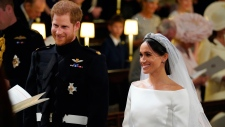 Prince Harry and Meghan Markle, during their wedding ceremony at St. George's Chapel in Windsor Castle in Windsor, near London, England, Saturday, May 19, 2018. (Gareth Fuller/pool photo via AP)
