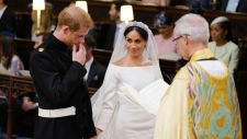 Prince Harry and Meghan Markle hold hands in St George's Chapel at Windsor Castle during their wedding service, conducted by the Archbishop of Canterbury Justin Welby in Windsor, near London, England, Saturday, May 19, 2018. (Dominic Lipinski / pool photo via AP)