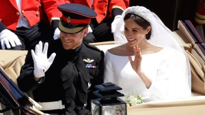 Prince Harry and Meghan Markle wave as they leave Windsor Castle in a carriage after their wedding ceremony at St. George's Chapel in Windsor Castle in Windsor, near London, England, Saturday, May 19, 2018. (AP Photo/Matt Dunham)