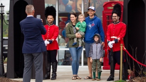 "Mike and Lindsay Tuckwood along with kids Hudson and Emmett pose for a photograph with some some of the ""Tim's Guards"" in front of a Tim Hortons in London, Ont., where fans of the royals came to watch the wedding of Meghan Markle and Prince Harry, the Duke and Duchess of Sussex, on Saturday, May 19, 2018. THE CANADIAN PRESS/ Geoff Robins"