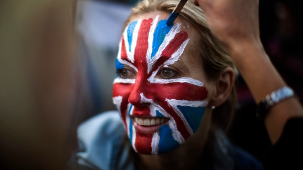 A woman is painted with a British flag on her face, as they wait at The Long Walk to watch the carriage procession after the wedding of Britain's Prince Harry and Meghan Markle at St. George's Chapel in Windsor Castle in Windsor, near London, England, Saturday, May 19, 2018. (AP Photo/Emilio Morenatti)