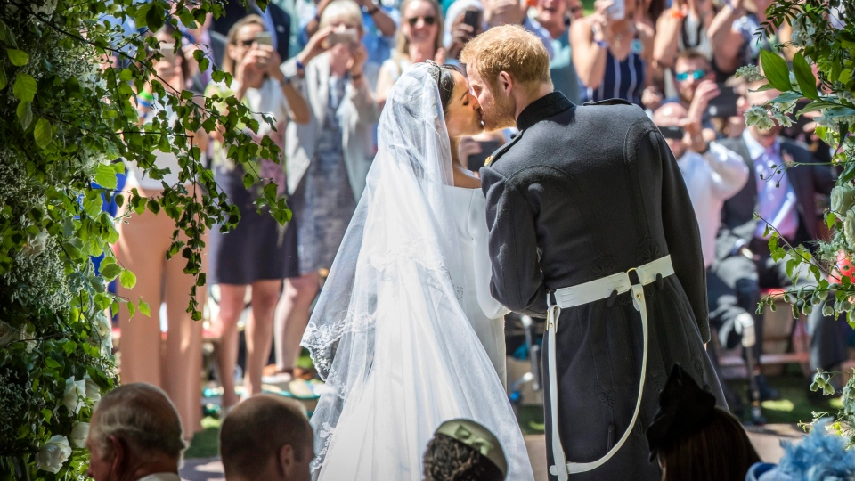 Meghan Markle and Prince Harry kiss on the steps of St George's Chapel at Windsor Castle following their wedding in Windsor Castle in Windsor, near London, England, Saturday, May 19, 2018. (Danny Lawson/pool photo via AP)