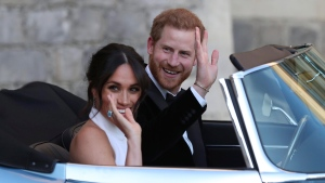 The newly married Duke and Duchess of Sussex, Meghan Markle and Prince Harry, leave Windsor Castle in a convertible car after their wedding in Windsor, England, to attend an evening reception at Frogmore House, hosted by the Prince of Wales, Saturday, May 19, 2018. (Steve Parsons/PA via AP)
