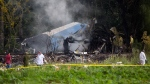 Investigators work near the smoldering remains of a Boeing 737 that plummeted into a yuca field just after takeoff with more than 100 passengers on board, in Havana, Cuba, Friday, May 18, 2018. (AP Photo/Desmond Boylan)