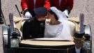 Britain's Prince Harry and Meghan Markle kiss as they ride in a carriage down the Long Walk after their wedding ceremony of Prince Harry and Meghan Markle at St. George's Chapel in Windsor Castle in Windsor, near London, England, Saturday, May 19, 2018. (Yui Mok/pool photo via AP)