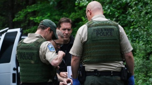 Washington State Fish and Wildlife Police confer with an individual from the King County Medical Examiner's and a King County Sheriff's deputy on a remote gravel road above Snoqualmie, WA., following a fatal cougar attack. Saturday May 19, 2018. (Alan Berner /The Seattle Times via AP)