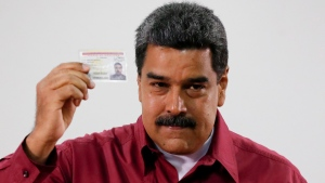 Venezuela's President Nicolas Maduro showed his ID after voting during presidential elections in Caracas, Venezuela, Sunday, May 20, 2018.  (AP Photo/Ariana Cubillos)