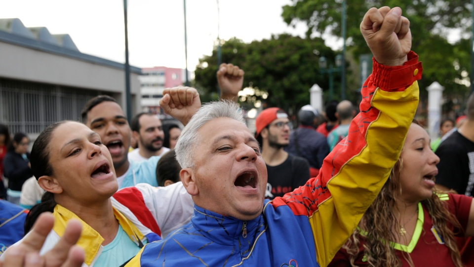 Supporters of Venezuela's President Nicolas Maduro cheer outside the polling station where his is voting during presidential elections in Caracas, Venezuela, Sunday, May 20, 2018. (AP Photo/Ricardo Mazalan)