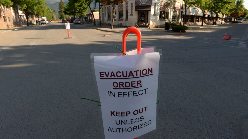 An evacuation sign is sits on a road in anticipation of flood waters in Grand Forks, in the Boundary Country of the West Kootenay region of British Columbia, on Tuesday, May 15, 2018. (THE CANADIAN PRESS/Jonathan Hayward)