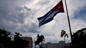 A Cuban flag is seen flying at half-mast near a statue of national hero Jose Marti, marking the start of two days of national mourning, in Havana, Cuba, Saturday, May 19, 2018. (AP Photo/Ramon Espinosa)