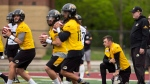 """The newest addition to the CFL Hamilton Tiger Cats roster, quarterback Johnny Manziel is seen with teammates on the field at McMaster University during Tiger Cats training camp in Hamilton, Ont., on Sunday, May 20, 2018. The former NFLer and Heisman Trophy winner signed a two-year deal with the Hamilton Tiger Cats to further his career after a long break calling the deal his """"best opportunity for me moving forward."""" THE CANADIAN PRESS/Peter Power"""