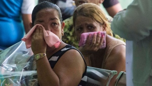Grieving relatives of passengers who perished in Cuba's worst aviation disaster wait for the identification of the bodies at the morgue in Havana, Cuba, Sunday, May 20, 2018. Officials say 110 people died when a charter passenger jet hired by Cuba's state-run airline, Cubana de Aviacion, crashed Friday in the rural outskirts of Havana. (AP Photo/Desmond Boylan)