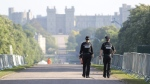 Two police officers make their way down the Long Walk in Windsor, England as the clean-up continues after the royal wedding of Prince Harry and Meghan Markle, Sunday May 20, 2018. (Andrew Matthews / PA via AP)