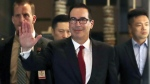 U.S. Treasury Secretary Steven Mnuchin, centre, waves to reporters as he arrives to a hotel after meeting with Chinese officials in Beijing, on May 3, 2018. (Andy Wong / AP)