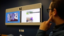 Jeff Wieland, right, Facebook director of accessibility, watches as engineer Matt King, who is blind, demonstrates facial recognition technology via a teleconference at Facebook headquarters in Menlo Park, Calif., on December 18, 2017. Based on recent announcements by the likes of Facebook, Live Nation and a U.K. police force, Canadians may need to get used to the idea of facial recognition technology permeating their everyday lives. THE CANADIAN PRESS/AP, Eric Risberg