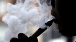 A man smokes an electronic cigarette in Chicago in this April 23, 2014 file photo. THE CANADIAN PRESS/AP/Nam Y. Huh, File