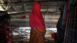 In this Monday, Nov. 20, 2017, photo, a 22-year-old woman who says she was raped by members of Myanmar's armed forces in June and again in September, clutches her hands around her pregnant belly as she is photographed in her tent in Kutupalong refugee camp in Bangladesh. (AP Photo/Wong Maye-E)