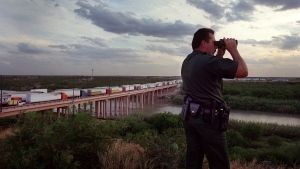 In this Aug. 8, 2001, file photo, U.S. Border Patrol supervisor Dan Garibay scans the Rio Grande for illegal immigrants and drug smugglers while overlooking the Laredo, Tx. International Bridge number 3, which crosses into Nuevo Laredo, Mexico. (AP Photo/John Moore)