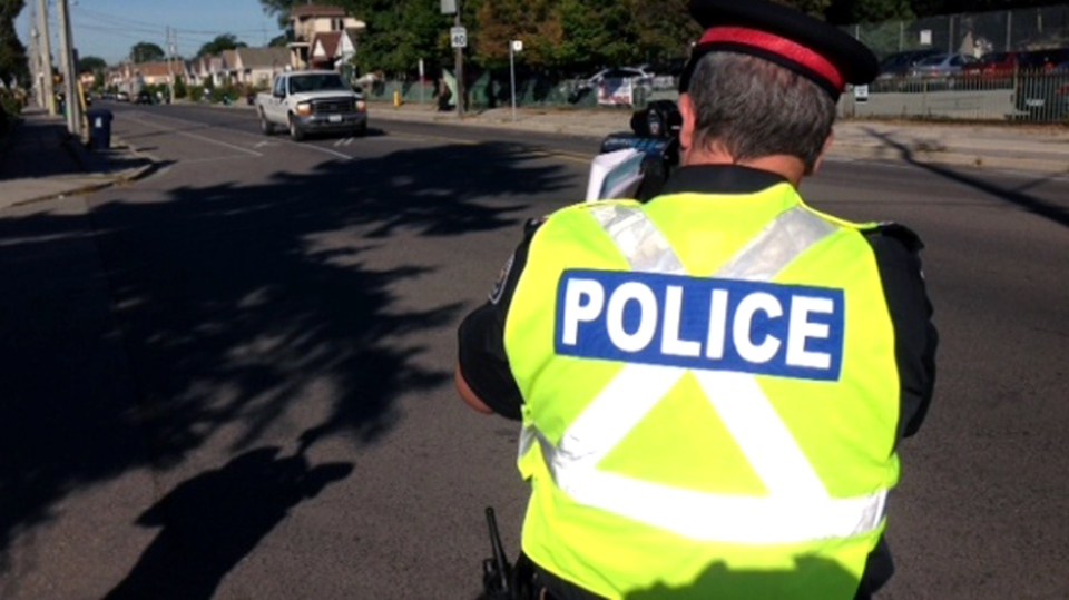 A police officer looks for speeders with a radar gun. (Cam Woolley/CP24)
