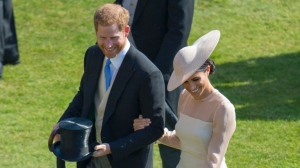 Meghan, the Duchess of Sussex walks with her husband Prince Harry during a garden party at Buckingham Palace in London, Tuesday May 22, 2018. (Ian Vogler/Pool Photo via AP)