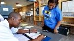 Election clerk Wayne Frazier, left, signs in Erika Skinner to vote Tuesday, May 22, 2018, at the Winburn precinct at Winburn Middle School, in Lexington, Ky. (Charles Bertram/Lexington Herald-Leader via AP)