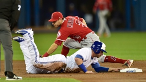 Toronto Blue Jays first baseman Justin Smoak (14) makes it back to second as Los Angeles Angels second baseman Ian Kinsler (3) misses the tag after teammate Jays center fielder Kevin Pillar (11) lined out to third in first inning American League baseball action in Toronto on Tuesday, May 22, 2018. THE CANADIAN PRESS/Frank Gunn