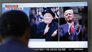 A man watches a TV screen showing file footage of U.S. President Donald Trump, right, and North Korean leader Kim Jong Un, left, during a news program at the Seoul Railway Station in Seoul, South Korea, Wednesday, May 23, 2018. (AP Photo/Lee Jin-man)