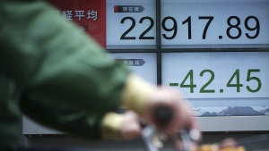 A man rides a bicycle past an electronic stock board showing Japan's Nikkei 225 index at a securities firm in Tokyo Wednesday, May 23, 2018. (AP Photo/Eugene Hoshiko)