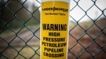 A sign warning of an underground petroleum pipeline is seen on a fence at Kinder Morgan's facility in Burnaby, B.C., on Monday April 9, 2018.  THE CANADIAN PRESS/Darryl Dyck