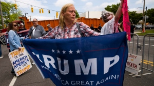 Joan Mills stands near the Morrelly Homeland Security Center, Wednesday, May 23, 2018, in Bethpage, N.Y. prior to the arrival of U.S. President Donald Trump who will speak to Homeland Security and law enforcement personnel. Mills, of Patchogue, N.Y., says she is not against immigrants, but wants them to arrive legally. (AP Photo/Mark Lennihan)