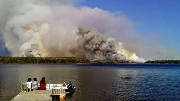 People from the Paungassi First Nation watch a fire burning in Little Grand Rapids, Man. in a handout photo provided by councillor Clinton Keeper of Little Grand Rapids.(THE CANADIAN PRESS/ HO-Clinton Keper)