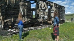 Archaeologist Kendra Kolomyja and Brenda McQueen, president of McDougall Stoney Mission Society, inspect the fire damaged church near Morley that could potentially be restored
