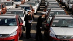 In this Jan. 14, 2015 photo, Chinese customs officials inspect cars being loaded for export at a port in Qingdao in eastern China's Shandong province. (Chinatopix via AP)