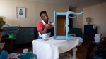 Kbre Hamilton, who runs an online business selling antique furniture, refinishes a table in his Hamilton apartment on Thursday, May 17, 2018. THE CANADIAN PRESS/Peter Power
